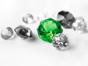 Green gemstone among colorless gemstones
