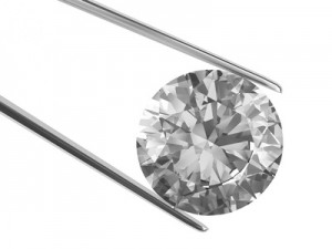 Close-up view on diamond in tweezers isolated on white